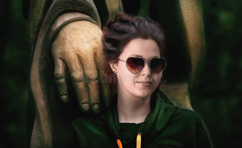 Belle femme avec des verres en forme de coeur et une statue en bois photographie stock