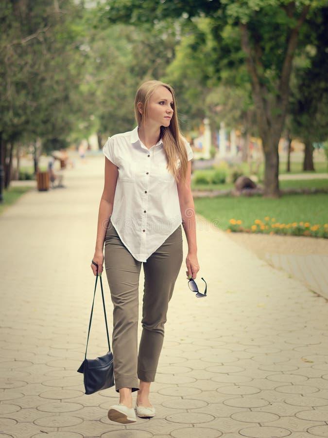 Belle femme avec des verres et un sac dans des ses mains seul marchant en parc photo stock