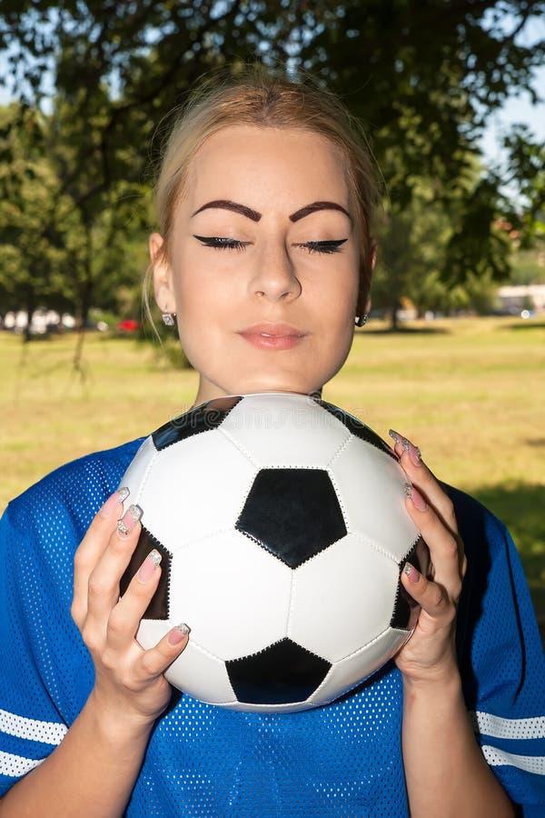 Belle femme avec du ballon de football image stock