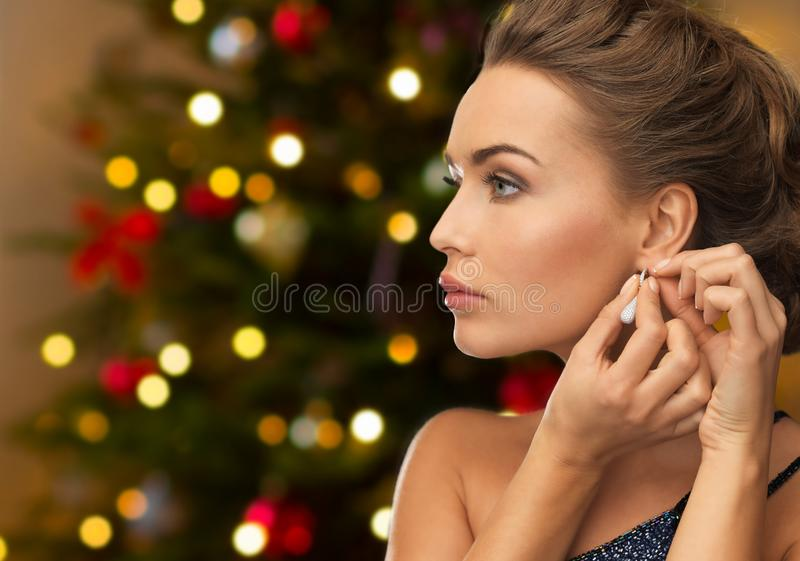 Belle femme avec la boucle d'oreille de diamant sur Noël photo libre de droits