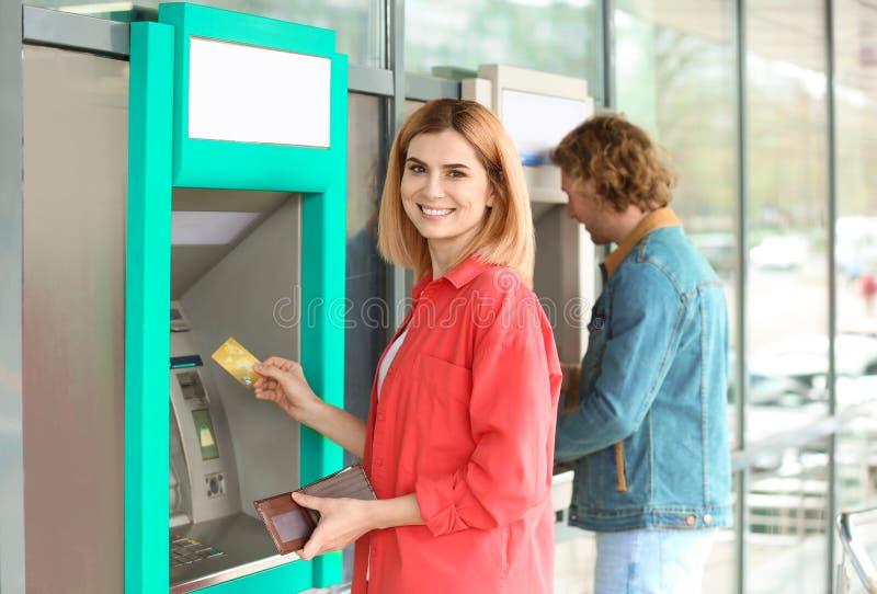 Belle femme avec la carte de crédit près du distributeur automatique de billets photos stock