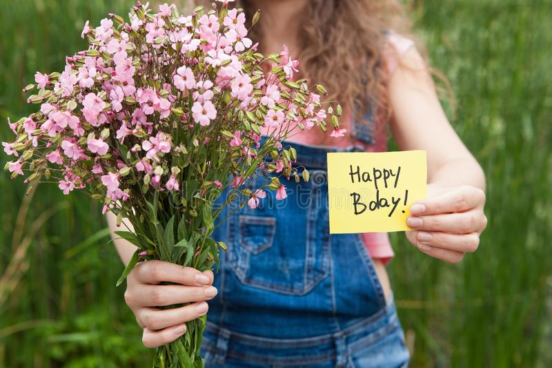 Belle femme avec la carte de joyeux anniversaire et le bouquet des fleurs roses image libre de droits