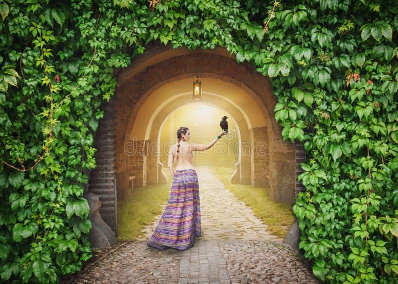 Belle femme avec la corneille sur la route ensoleillée mystérieuse photos libres de droits