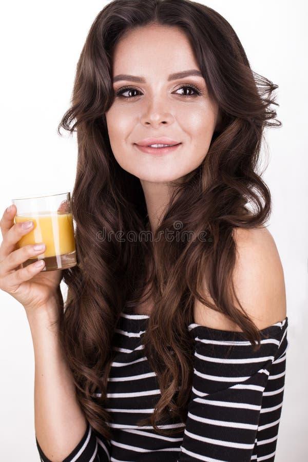 Belle femme avec la peau, les boucles saines de cheveux et le jus d'orange, posant dans le studio Visage de beauté images libres de droits