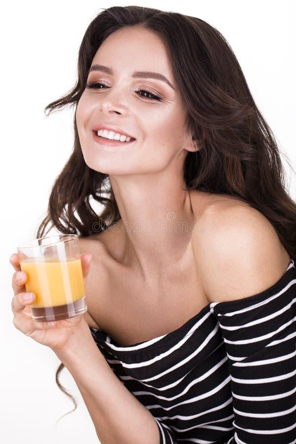 Belle femme avec la peau, les boucles saines de cheveux et le jus d'orange, posant dans le studio Visage de beauté photo libre de droits