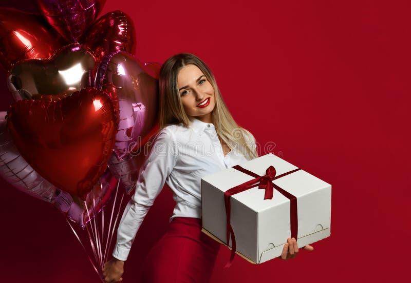 Belle femme avec le boîte-cadeau actuel et sourire heureux de ballons roses pourpres de coeur sur le fond rouge photo libre de droits