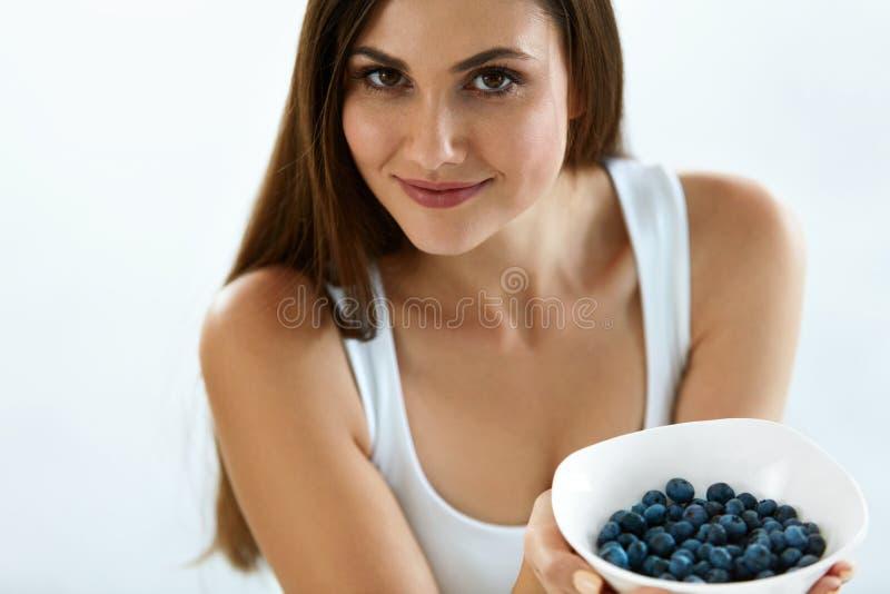 Belle femme avec le bol de myrtilles Nutrition d'alimentation saine photographie stock libre de droits