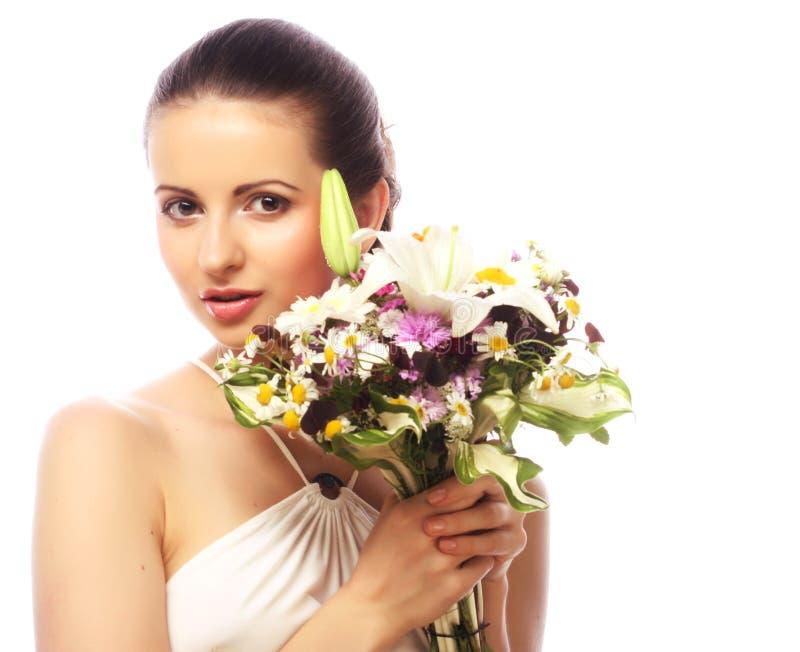 Belle femme avec le bouquet de différentes fleurs image stock