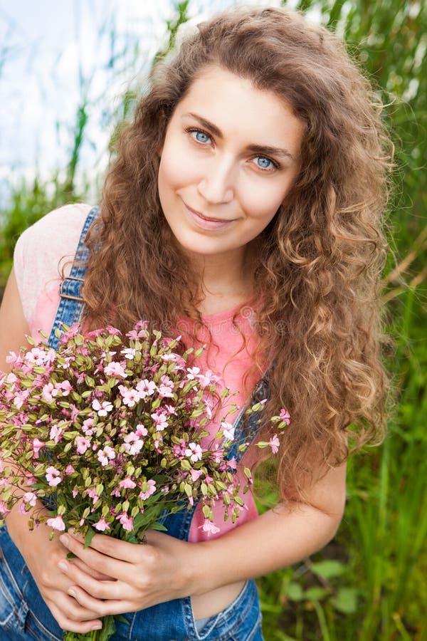 Belle femme avec le bouquet du sourire rose de fleurs photo stock