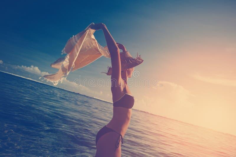 Belle femme avec le châle dans l'océan au coucher du soleil image stock