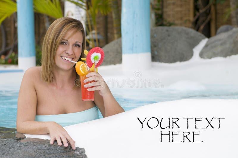 Belle femme avec le cocktail dans une piscine photographie stock