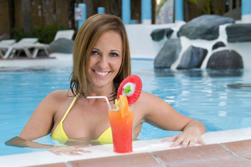 Belle femme avec le cocktail dans une piscine image libre de droits