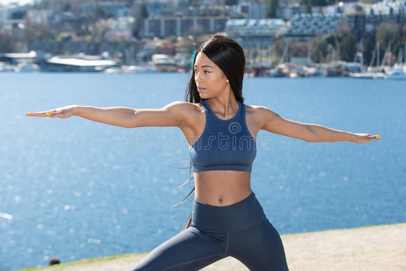 Belle femme avec le long soutien-gorge de port de pantalon et de sports de yoga de cheveux noirs ext?rieur pendant la s?ance d'en image libre de droits
