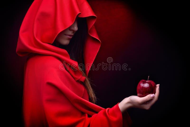 Belle femme avec le manteau rouge tenant la pomme photo libre de droits