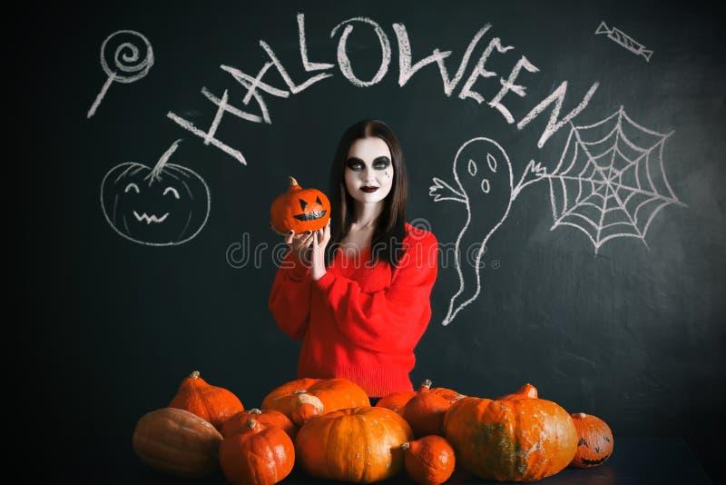 Belle femme avec le maquillage de Halloween et potirons près de mur foncé image stock