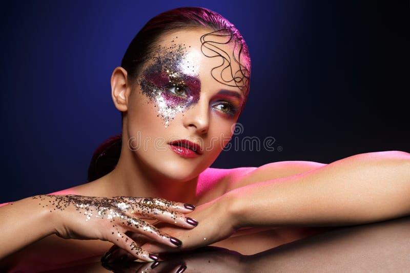Belle femme avec le maquillage lumineux avec le scintillement photographie stock libre de droits