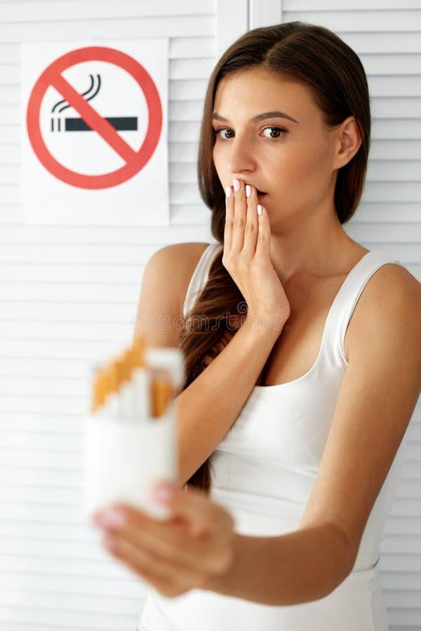 Belle femme avec le paquet des cigarettes et du signe non-fumeurs photo stock