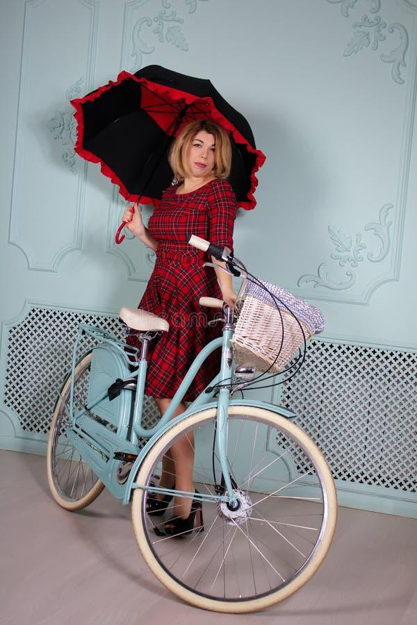 Belle femme avec le parapluie tenant la bicyclette proche photographie stock