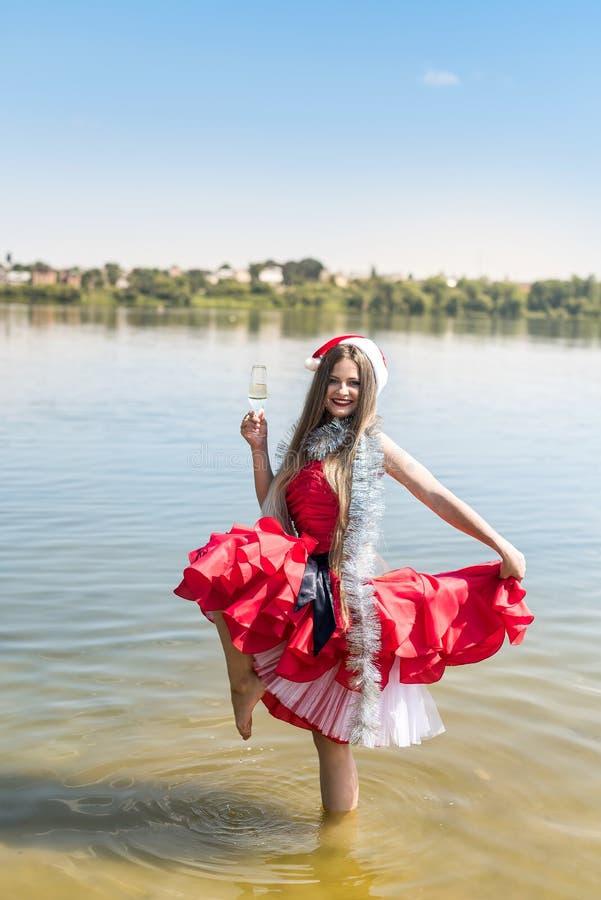 Belle femme avec le verre de champagne se tenant dans l'eau image libre de droits