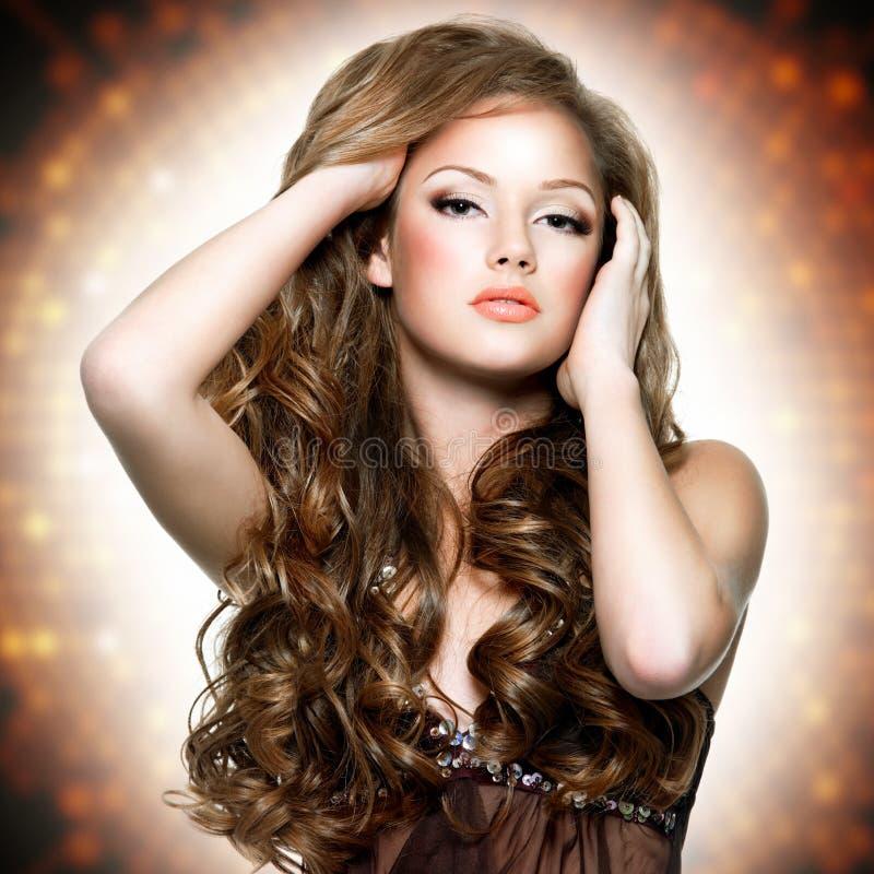 Belle femme avec le visage attrayant et les longs poils bouclés image stock
