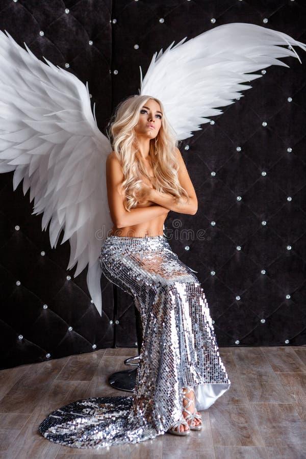 Belle femme avec les ailes blanches sur le fond noir photo stock