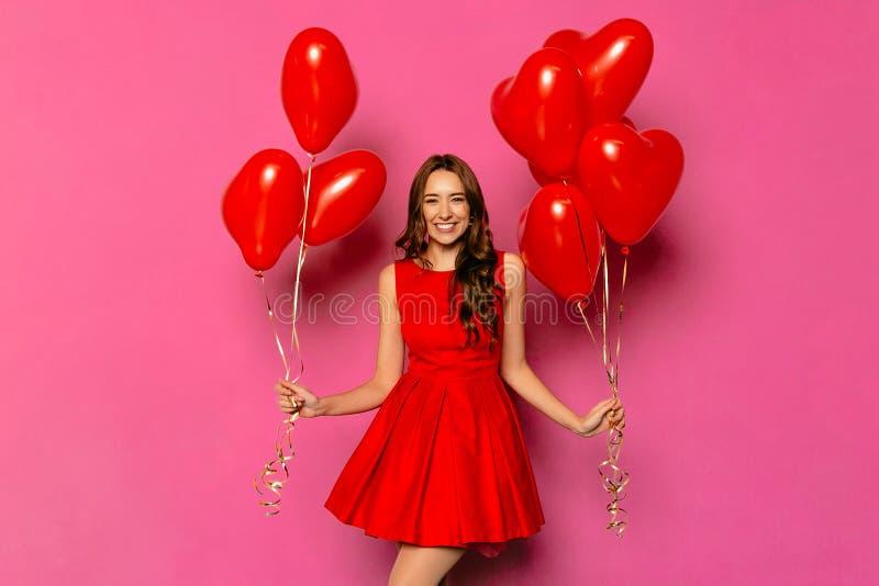 Belle femme avec les ballons à air en forme de coeur le jour du ` s de Valentine photo stock