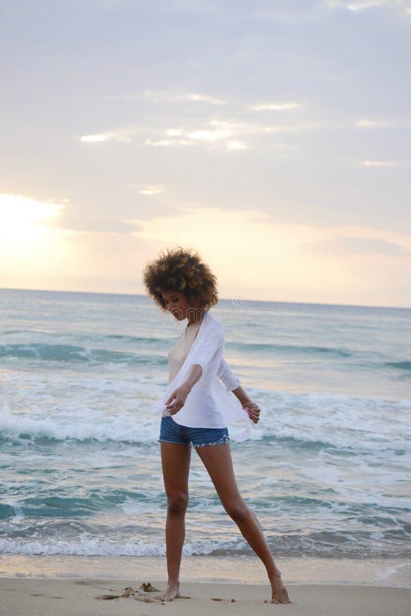 Belle femme avec les cheveux Afro ayant l'amusement au coucher du soleil sur la mer image libre de droits