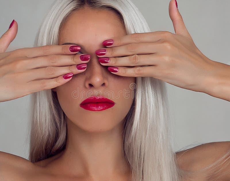 Belle femme avec les cheveux blonds Mannequin avec le rouge à lèvres rouge et les clous rouges images libres de droits