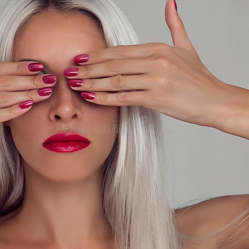 Belle femme avec les cheveux blonds Mannequin avec le rouge à lèvres rouge et les clous rouges image stock