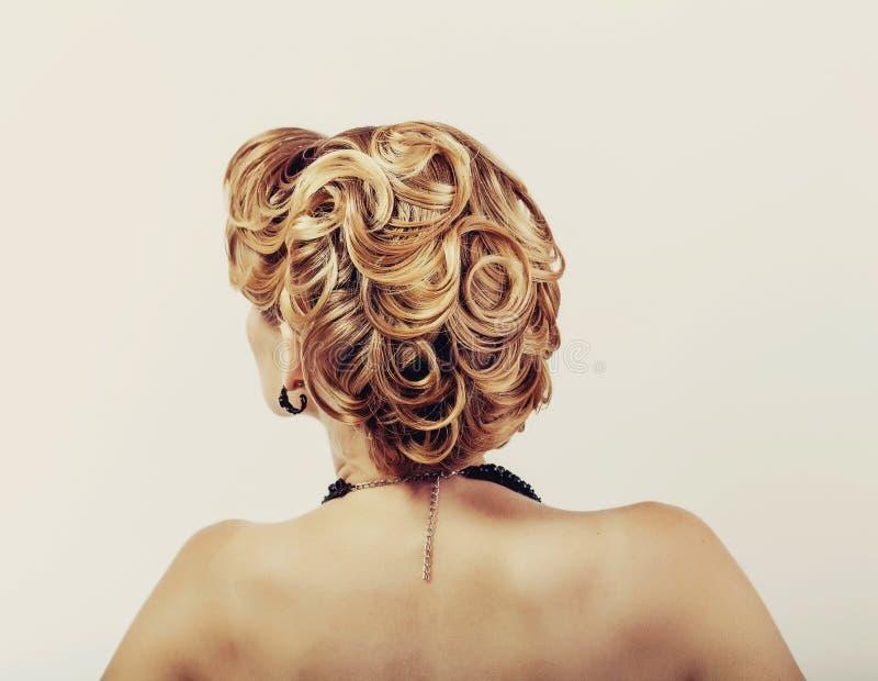 Belle femme avec les cheveux blonds portant la robe peu noire touchant sa vue de cou du dos sur le blanc photos stock