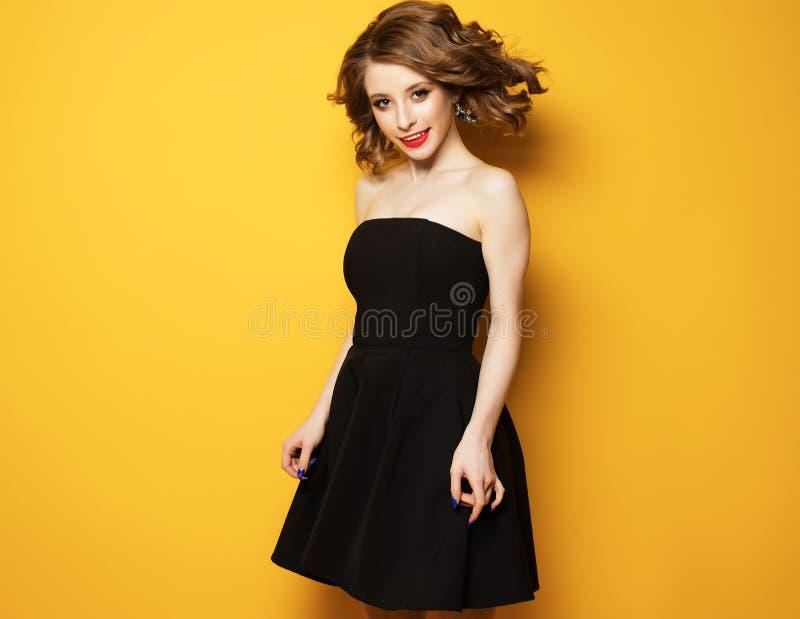 Belle femme avec les cheveux bouclés blonds dans la robe noire au-dessus du fond jaune photo stock