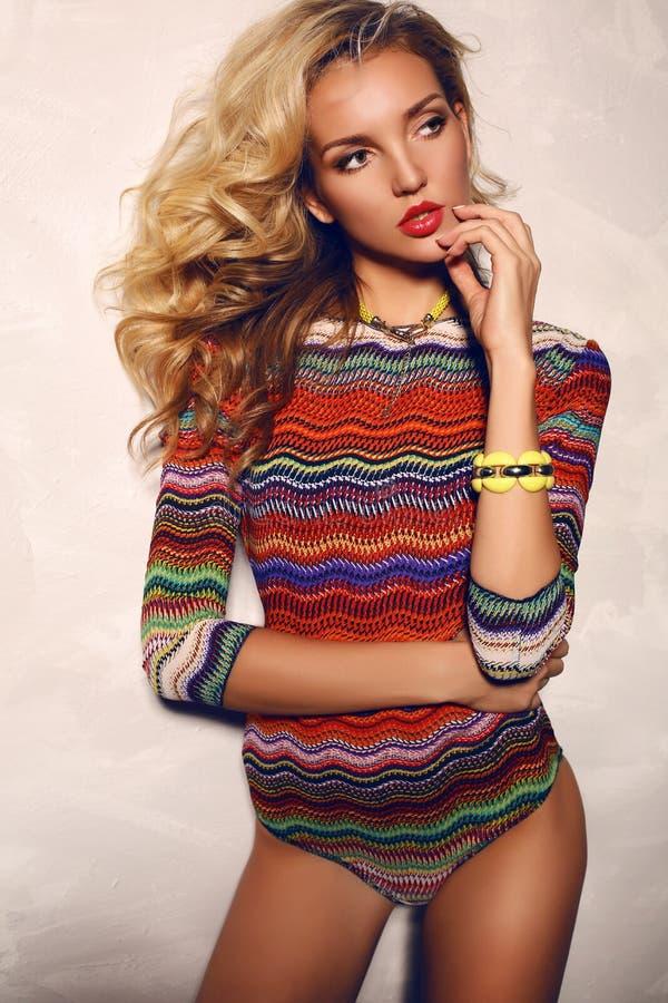 Belle femme avec les cheveux bouclés blonds utilisant le maillot de bain coloré photo stock
