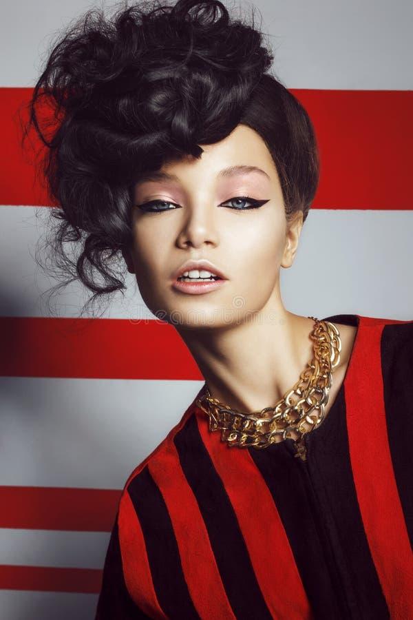 Belle femme avec les cheveux bouclés sur un rouge blanc rayé photos stock