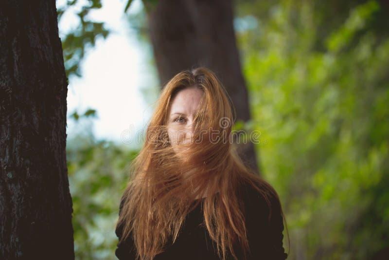 Belle femme avec les cheveux embrouillés posant en parc d'automne photographie stock libre de droits