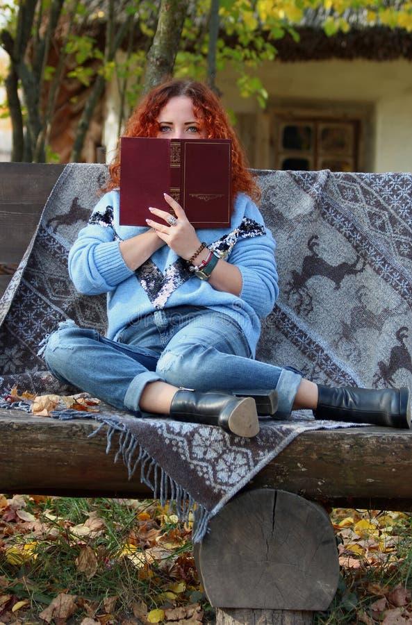 Belle femme avec les cheveux rouges en parc d'automne se reposer sur un banc avec un voile et couvert de son visage de livre Back photos libres de droits
