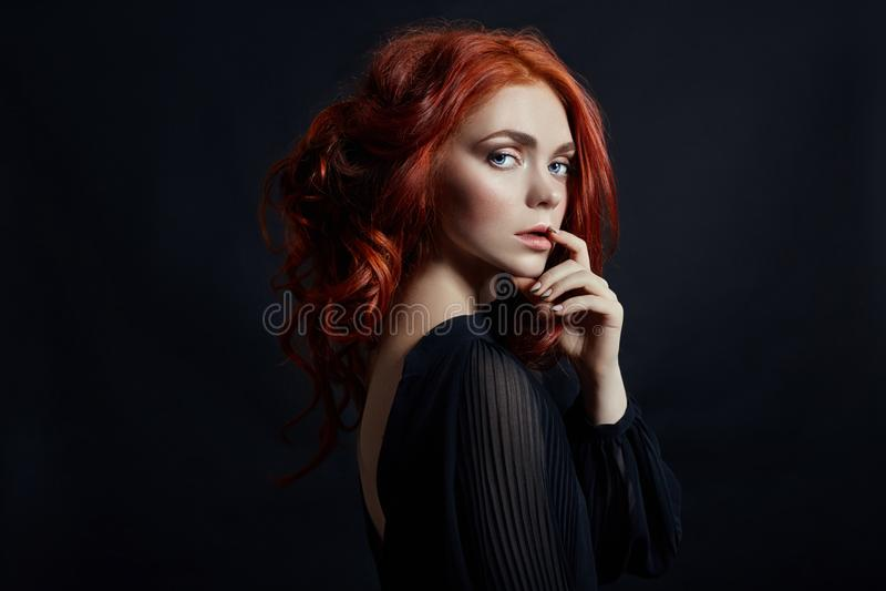 Belle femme avec les cheveux rouges sur un fond noir Portrait d'une femme réussie, peau pure, maquillage naturel, visage de soins photos stock