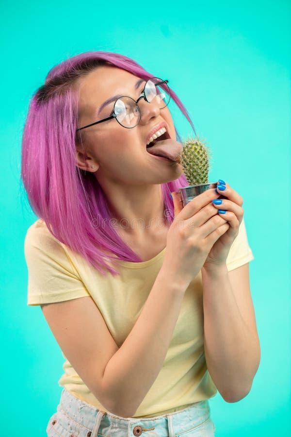 Belle femme avec les cheveux violets tenant le cactus dans le pot et des épines émouvantes image stock