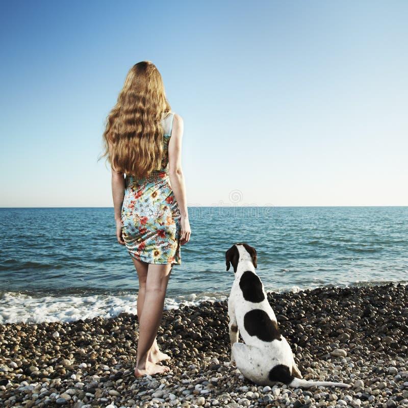 Belle femme avec un crabot sur la plage image stock