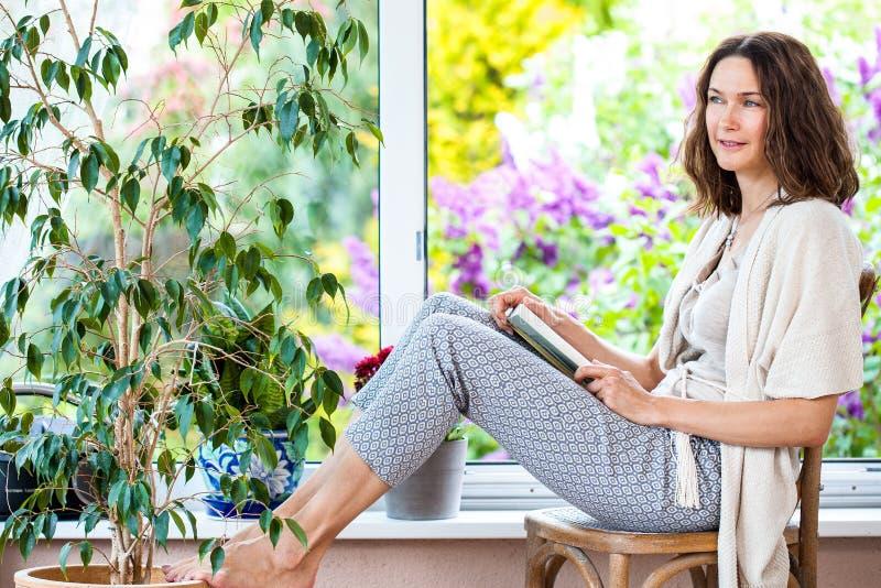 Belle femme avec un livre près de la fenêtre photographie stock libre de droits