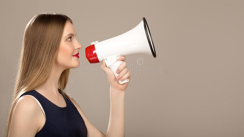Belle femme avec un mégaphone à disposition Copycpase photos stock