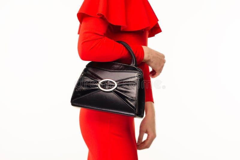 Belle femme avec un sac à main noir dans ses mains et robe égalisante rouge photo stock