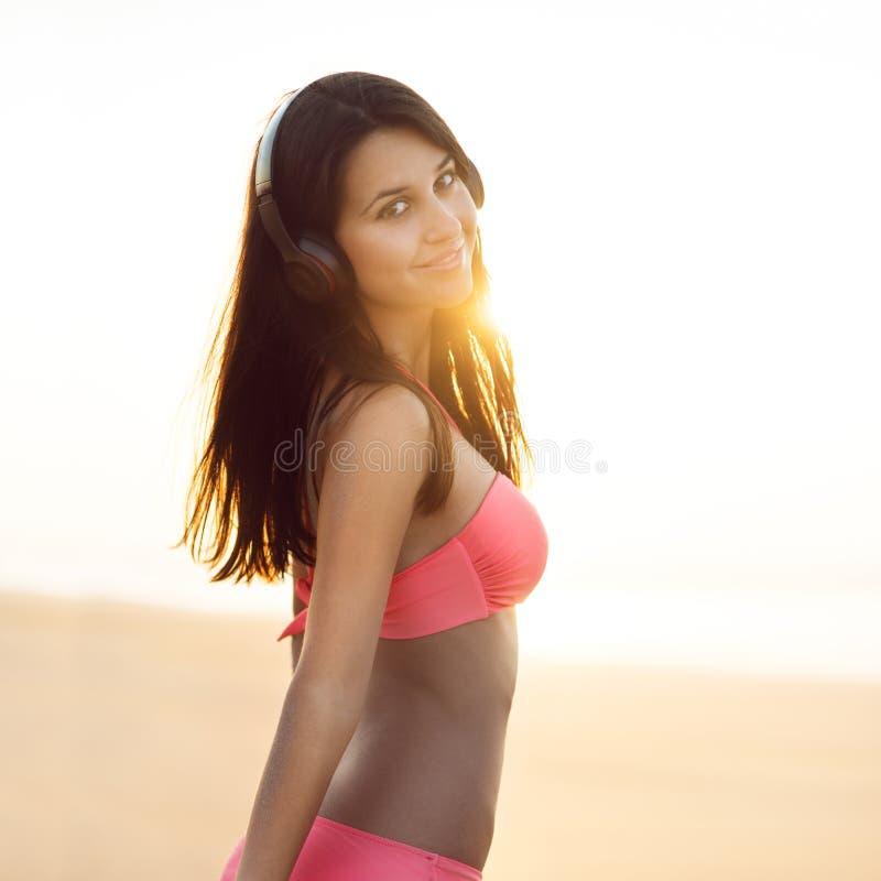 Belle femme ayant l'amusement à l'été sur la danse de plage d'océan dans le maillot de bain et la musique de écoute utilisant les photos stock