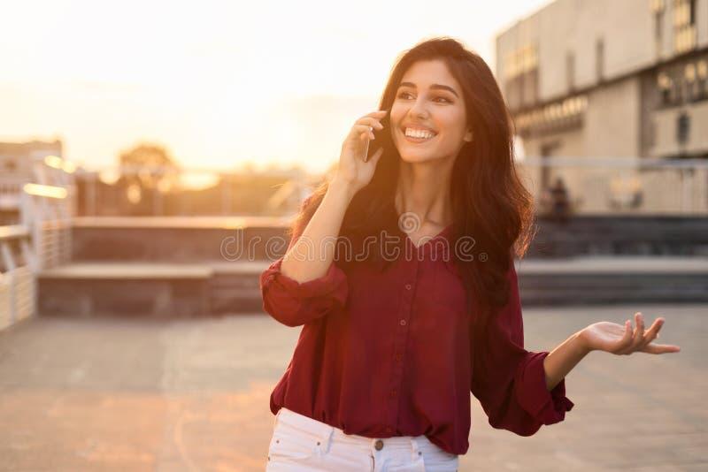 Belle femme ayant l'entretien de téléphone dehors, marchant dans la ville photo libre de droits