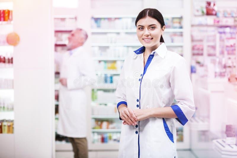 Belle femme ayant un jour ouvrable dans une pharmacie photos stock