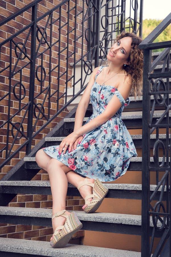 Belle femme bien-toilettée dans une robe bleue posant sur les escaliers avec les balustrades tordues image libre de droits