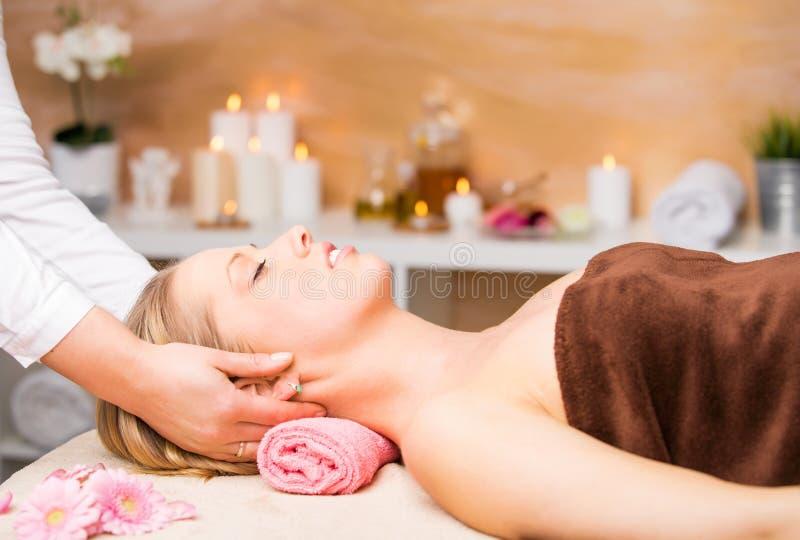 Belle femme blonde atteignant le massage facial la station thermale photo stock
