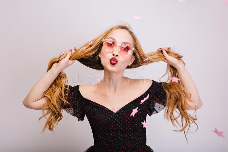 Belle femme blonde avec de longs cheveux bouclés dans des mains ayant l'amusement, fille gaie donnant le baiser à la caméra, semb image stock