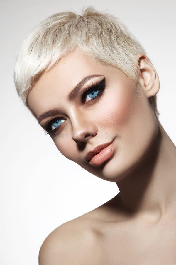 Belle femme blonde avec la coupe de cheveux courts et ey à ailes élégant photo libre de droits