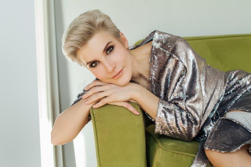 Belle femme blonde avec la séance de cheveux courts image stock