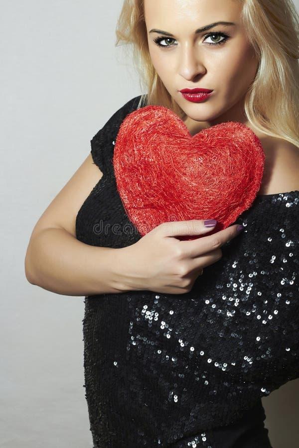 Belle femme blonde avec le coeur rouge. Fille de beauté. Montrez le symbole d'amour. Saint-Valentin. Robe noire photos stock